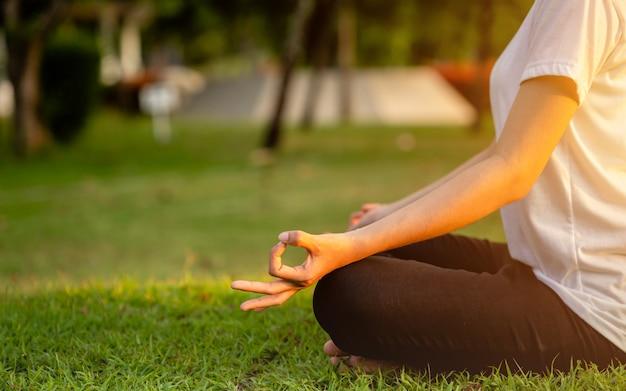 Mujer asiática haciendo ejercicios de yoga en el parque