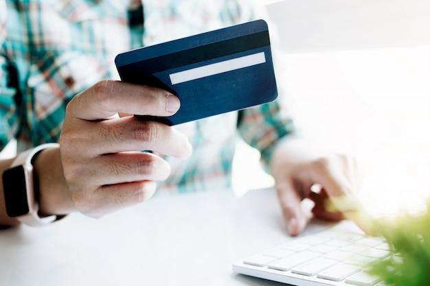 Mujer asiática haciendo pagos en línea en la computadora portátil con tarjeta de crédito