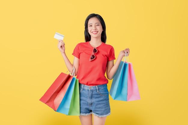 Mujer asiática hermosa alegre que sostiene bolsos de compras y la tarjeta de crédito multicolores en fondo amarillo claro.