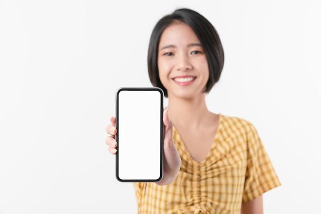 Mujer asiática hermosa alegre que sostiene smartphone en la pared blanca. lleva tu pantalla para poner publicidad.