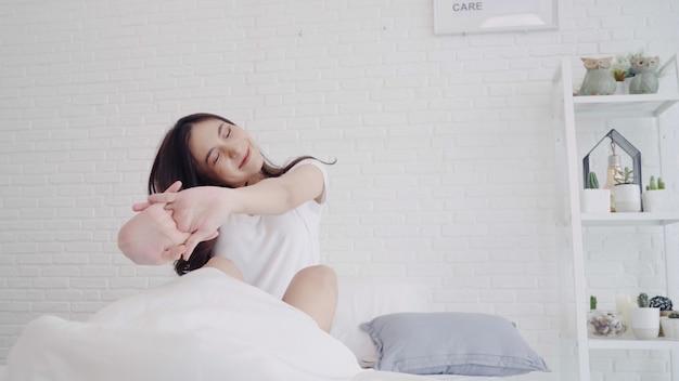 La mujer asiática hermosa feliz despierta, sonriendo y estirando sus brazos en su cama en el dormitorio.