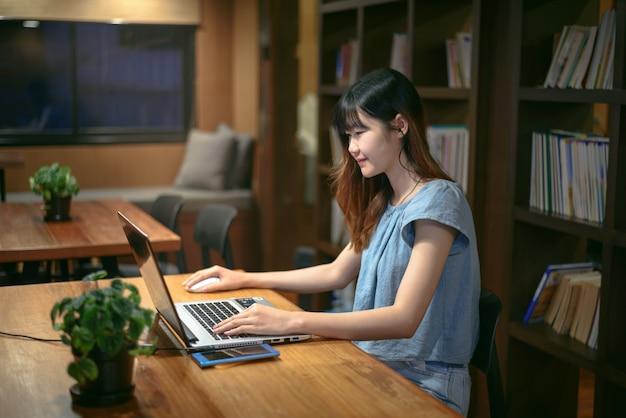 Mujer asiática hermosa feliz del estudiante que trabaja en el ordenador portátil en sitio moderno de la biblioteca