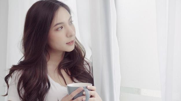 Mujer asiática hermosa feliz que sonríe y que bebe una taza de café o de té cerca de la ventana en el dormitorio.