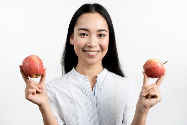 Mujer asiática hermosa joven que muestra dos manzanas rojas delante del fondo blanco