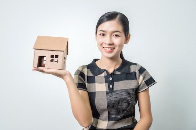 Mujer asiática hermosa joven que sostiene una casa en sus manos, pelos negros.