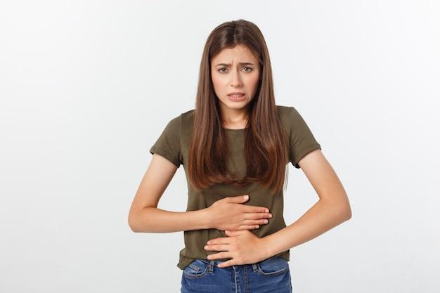 Mujer asiática hermosa joven que tiene dolor de estómago doloroso en blanco.
