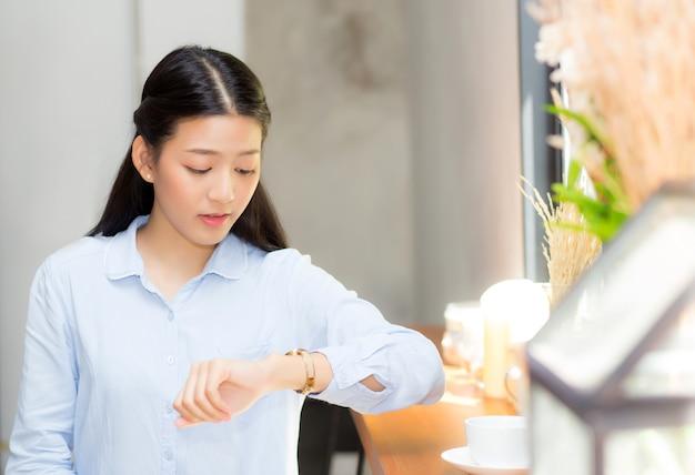 La mujer asiática hermosa mira el reloj que espera al amigo oa alguien.