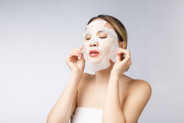 Mujer asiática hermosa que aplica la máscara de papel de la hoja en su fondo del blanco de la cara