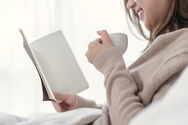 Mujer asiática hermosa que disfruta de café caliente y del libro de lectura en cama en su dormitorio