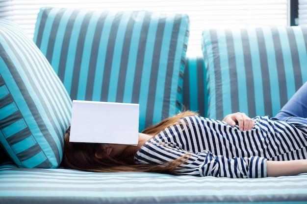 Mujer asiática hermosa que duerme en el sofá con el libro que cubre su cara