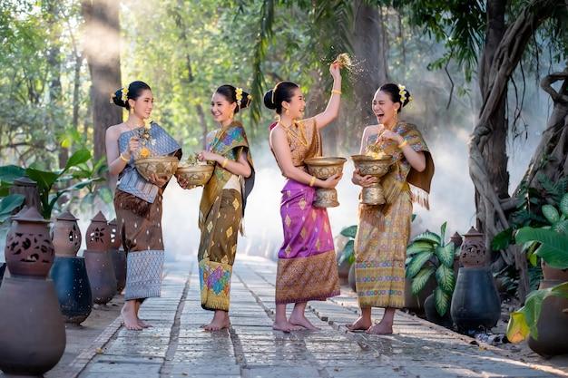 Mujer asiática hermosa que salpica el agua durante el festival tailandés, festival de songkran de la tradición.