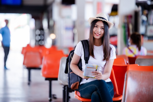 Mujer asiática hermosa que sonríe con el mapa y el bolso en la estación de autobuses