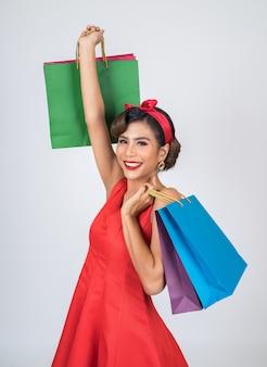 Mujer asiática hermosa que sostiene bolsos de compras coloreados