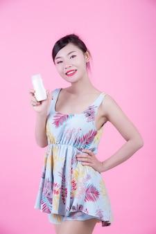 Mujer asiática hermosa que sostiene una botella de producto en un fondo rosado.