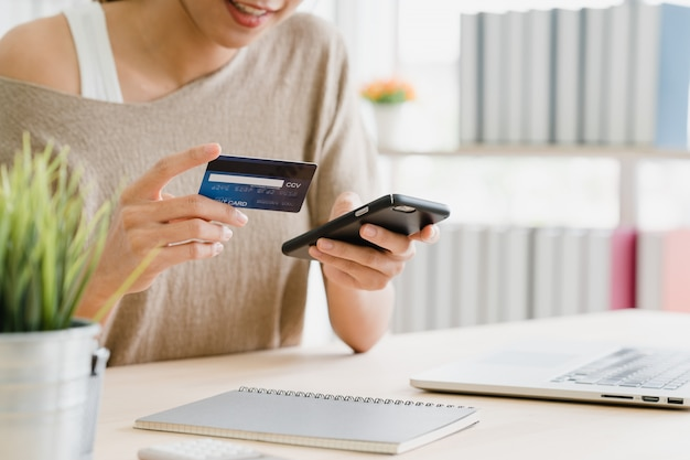 Mujer asiática hermosa que usa el teléfono inteligente que compra compras en línea