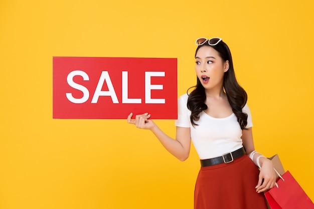 Mujer asiática hermosa sorprendida que muestra la muestra roja de la venta