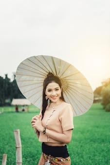 Mujer asiática hermosa en el vestido local que sostiene la situación de papel del paraguas