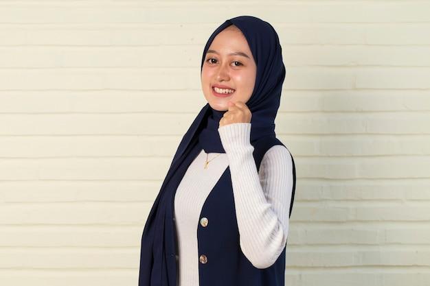 Mujer asiática con hijab feliz y emocionada celebrando la victoria expresando gran éxito