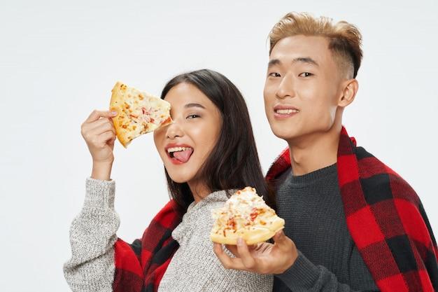 Mujer asiática y hombre comiendo pizza