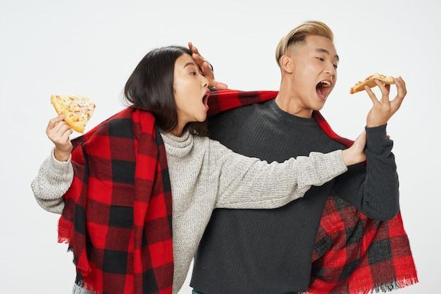 Mujer asiática y hombre comiendo rebanadas de pizza