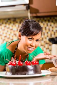 Mujer asiática hornear pastel de chocolate en la cocina