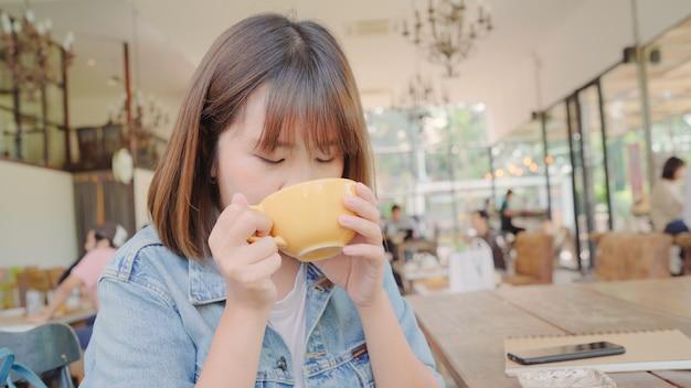 Mujer asiática independiente del negocio que bebe la taza caliente de té verde o de café mientras que se sienta en la tabla en café.