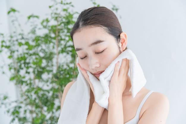 Mujer asiática (japonesa) vistiendo la cara con una toalla de baño blanca