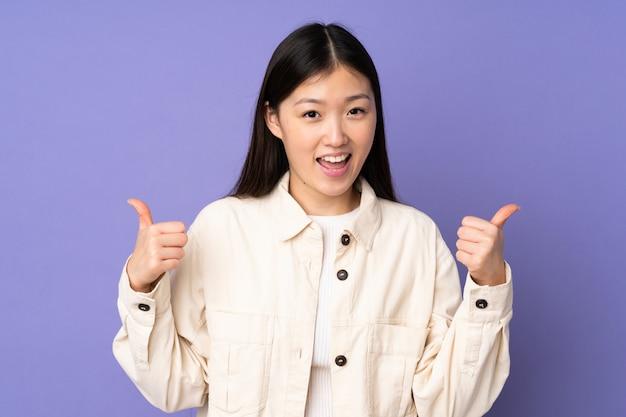 Mujer asiática joven aislada en púrpura dando un gesto de pulgares arriba