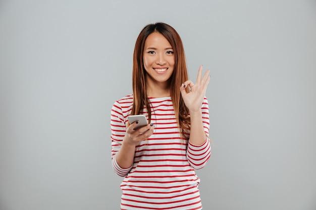 Mujer asiática joven alegre que charla por el teléfono que muestra gesto aceptable.