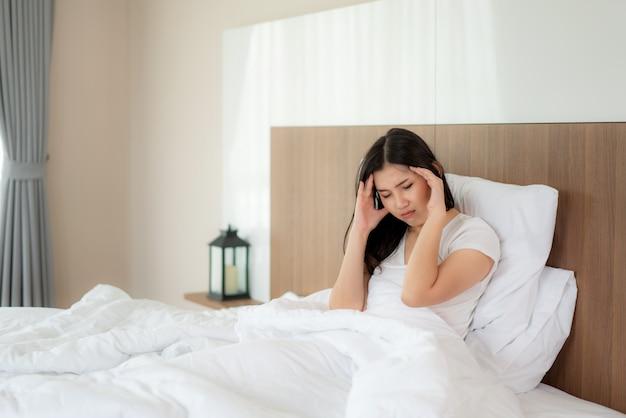 La mujer asiática joven atractiva se despierta en su cama sosteniendo su mano del dolor de cabeza y parece infeliz y siente dolor de cabeza / migraña / estrés / enfermo. concepto de salud de la mujer.