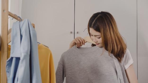 La mujer asiática joven atractiva hermosa que elige su equipo de la moda viste en armario en casa