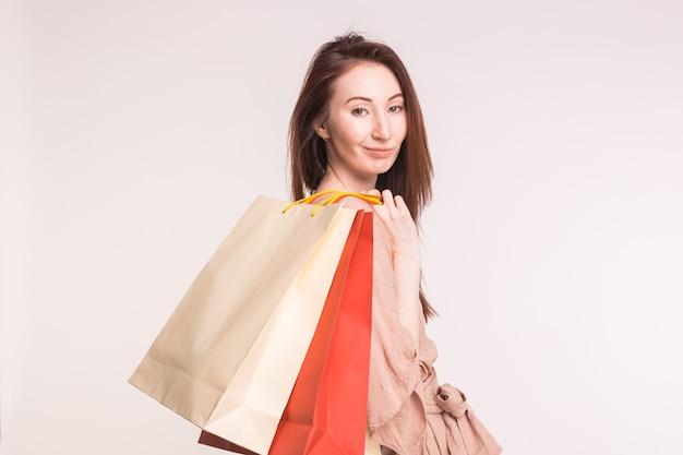 Mujer asiática joven bastante feliz con la compra en bolsas de papel en la pared blanca