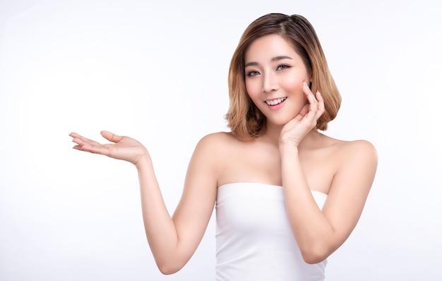 Mujer asiática joven de la belleza que muestra la mano para el producto en blanco.