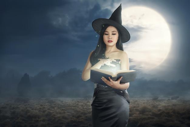 Mujer asiática joven de la bruja que lee los libros del encanto