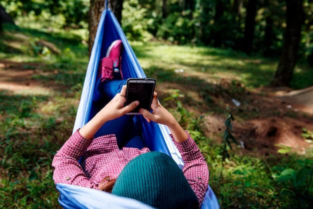 Mujer asiática joven del caminante que usa el teléfono móvil mientras que se relaja en hamaca