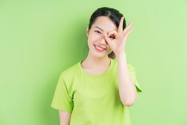 Mujer asiática joven con camisa verde y posando sobre fondo verde
