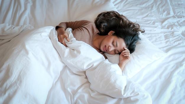 Mujer asiática joven en camisetas sencillas en la cama blanca de lujo.