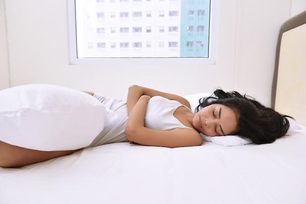 Mujer asiática joven con comodidad en cama