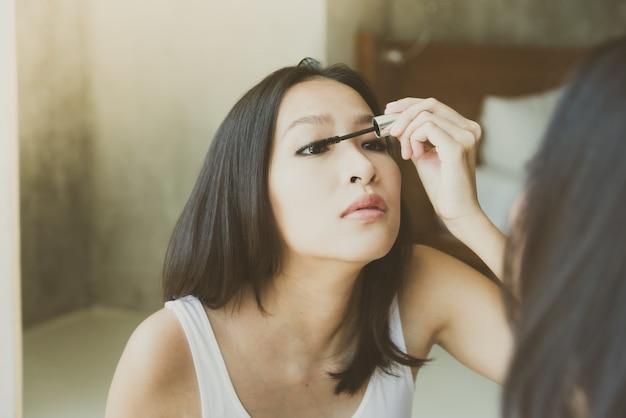 La mujer asiática joven se compone