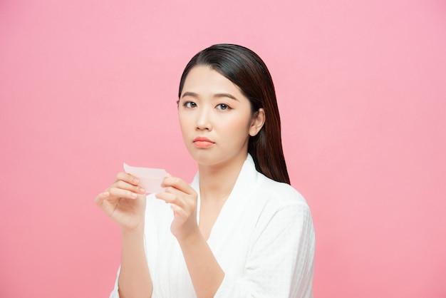 Mujer asiática joven del cuidado de la piel molesta después de usar papel secante de aceite en su cara