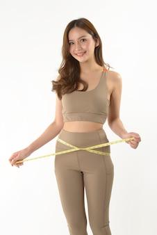 Mujer asiática joven delgada que mide de su cuerpo