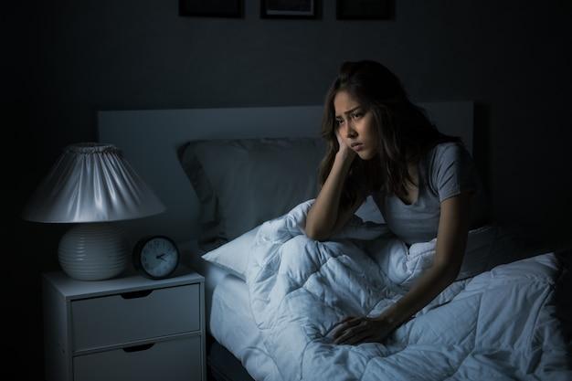 Mujer asiática joven deprimida sentada en la cama no puede dormir por insomnio