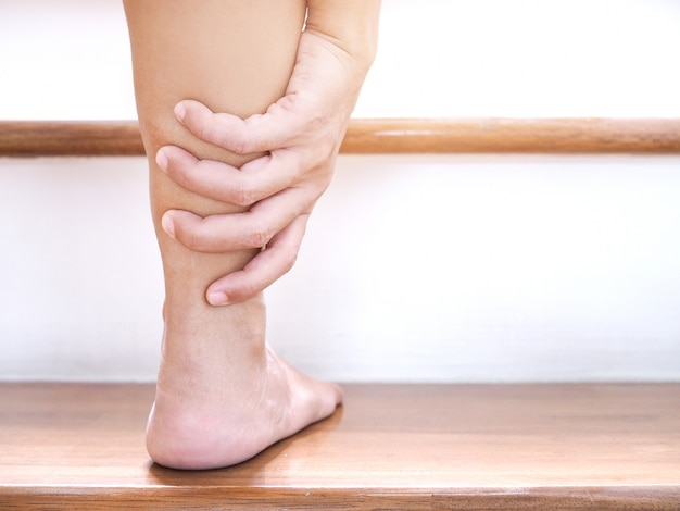 Mujer asiática joven con dolor en el tobillo y lesión aguda en la pierna al subir escaleras.
