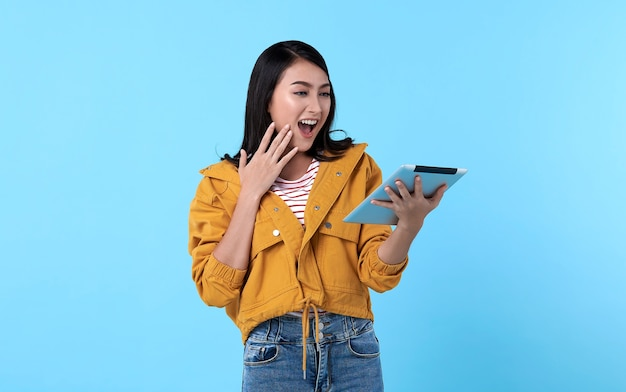 Mujer asiática joven emocionada que usa la tableta aislada en la pared azul