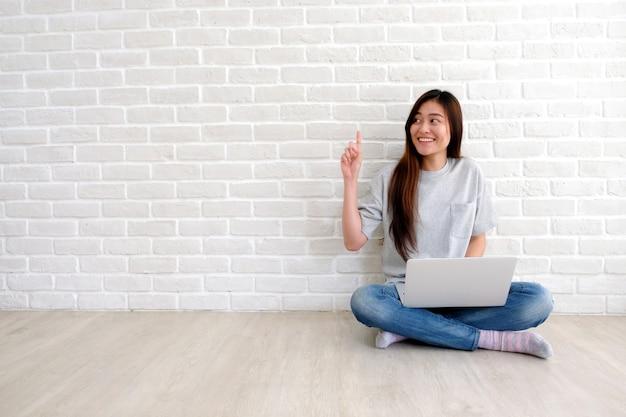 Mujer asiática joven en estilo ocasional usando la computadora de computadora portátil en el sitio blanco
