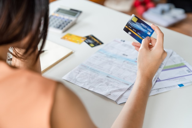 Mujer asiática joven estresada que sostiene la tarjeta de crédito y sin dinero para pagar la deuda de la tarjeta de crédito