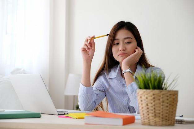 Mujer asiática joven con la expresión frustrada mientras que trabaja con el ordenador portátil