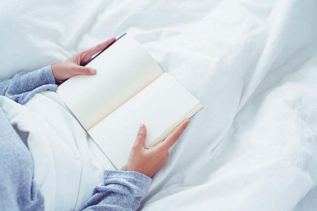 Mujer asiática joven feliz de la forma de vida que disfruta de mentir en el placer del libro de lectura de la cama en la ropa casual