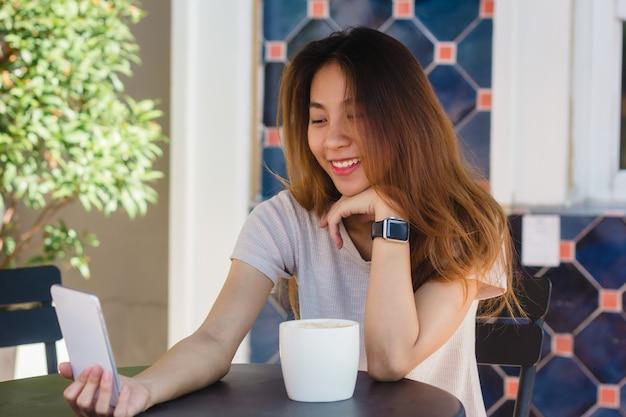 Mujer asiática joven feliz hermosa atractiva que toma un selfie usando un teléfono elegante en el café