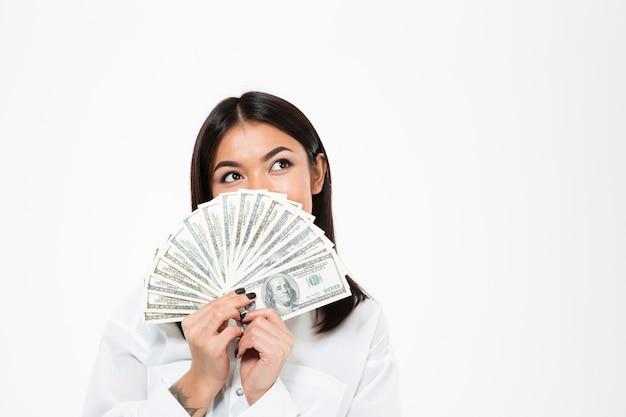 Mujer asiática joven feliz que cubre la cara con el dinero.